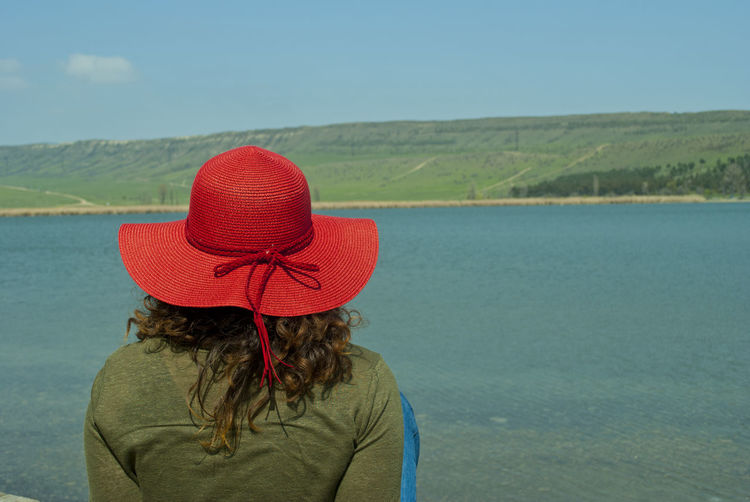Rear View Of Woman In Red Hat Sitting Against Lake