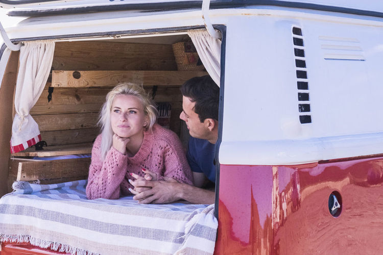 Smiling Young Couple Relaxing In Camper Van