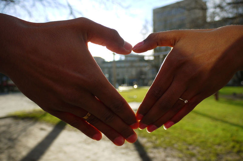Cropped Hands Of Couple Making Heart Shape In City
