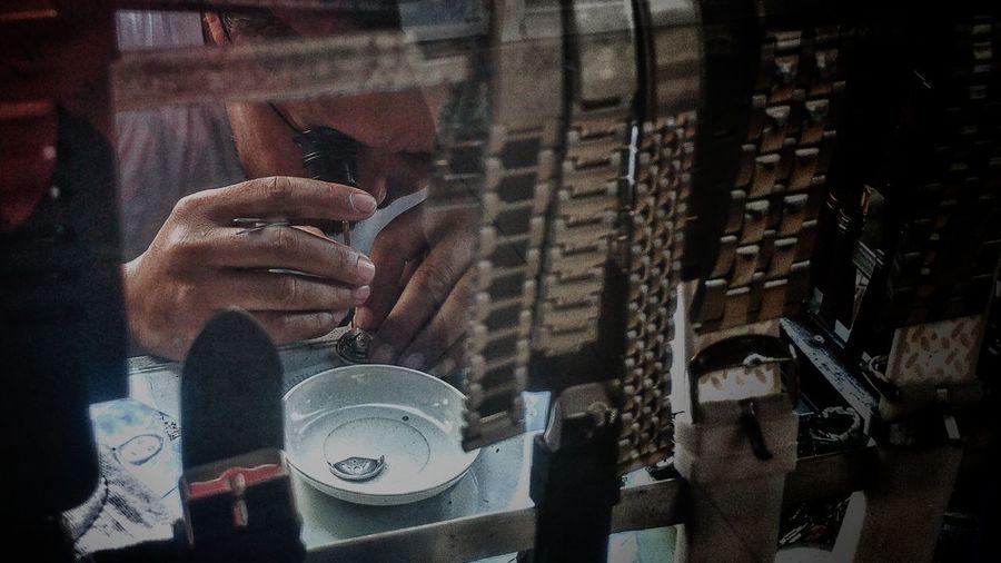 Man Repairing Wristwatch Seen Through Window