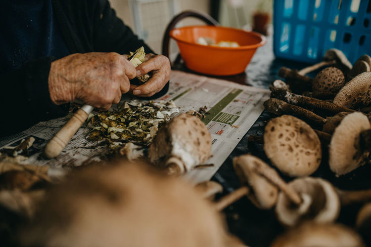 High angle view of senior woman preparing mushrooms on table