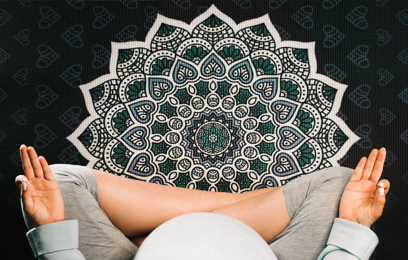 Pregnant woman sitting in lotus position on mandala yoga mat and meditating. Top view Human Body Part Pattern Young Adult Adult Indoors  Hand Human Hand One Person Body Part Sitting High Angle View Women Leisure Activity Relaxation Creativity Young Women Casual Clothing Design Low Section Floral Pattern Human Limb Yoga Meditation Mandala Pregnant