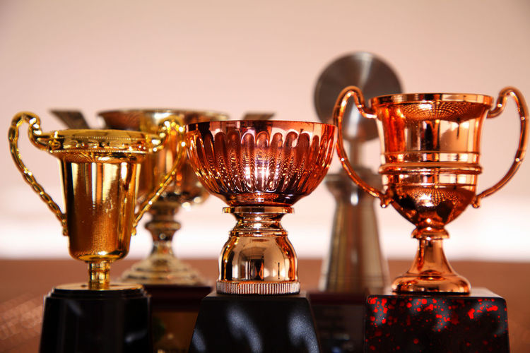 Close-up of trophies on table against wall