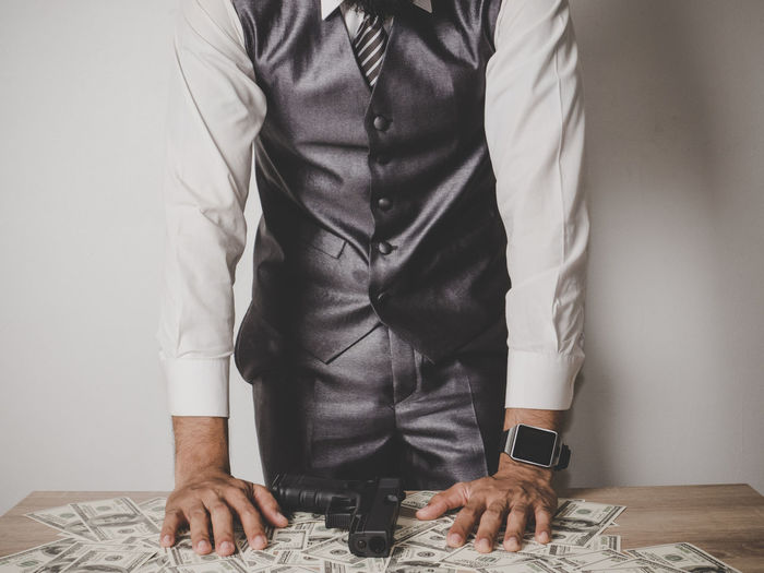 Midsection Of Businessman With Paper Currencies And Gun