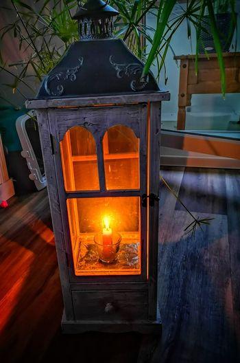 Close-up of illuminated lantern on wooden table