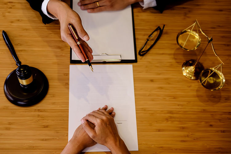 Cropped hands of male lawyer discussing with customer in office