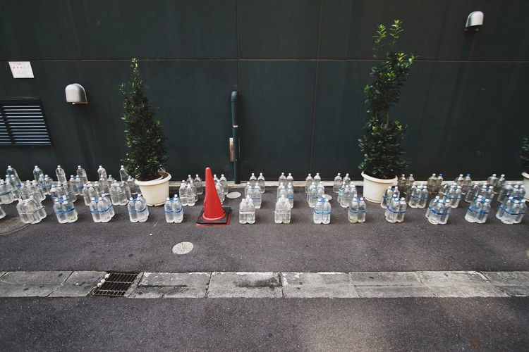 High angle view of water bottles on sidewalk by wall
