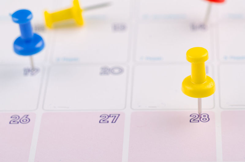 close up of colorful pin on calendar Indoors  No People Text Communication Close-up Yellow Western Script Reminder High Angle View Pill Number Paper Still Life Letter Full Frame Selective Focus Healthcare And Medicine Group Of Objects Dose Medicine