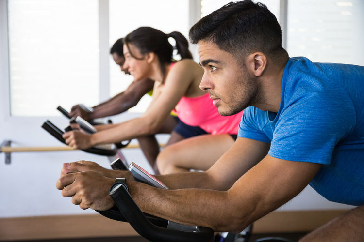 Athletes Cycling On Exercise Bike In Gym