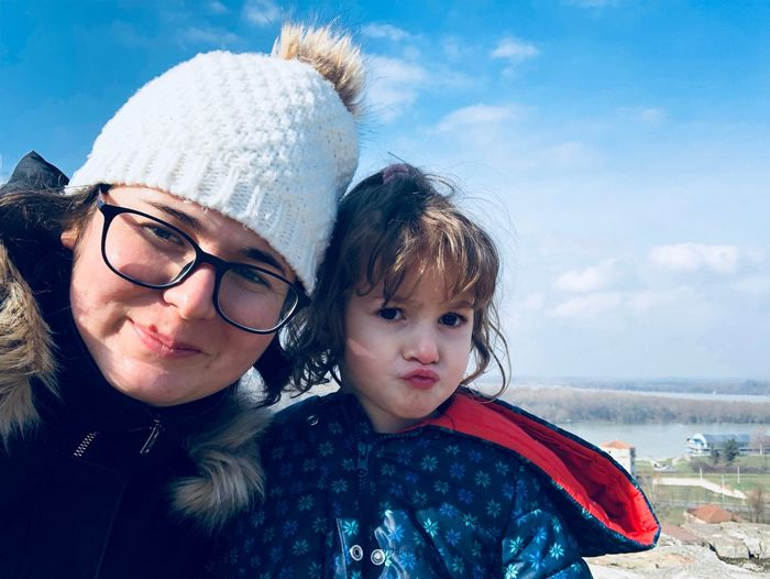 Portrait of happy mother and daughter against sky during winter