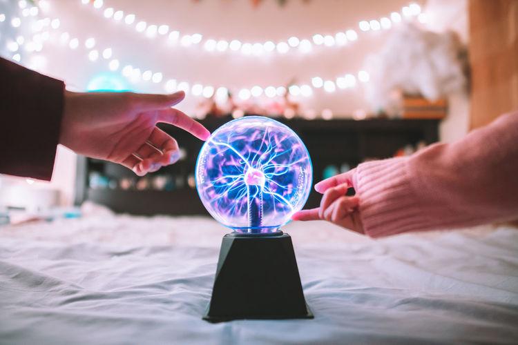 Cropped Image Of Woman Hand Around Plasma Ball