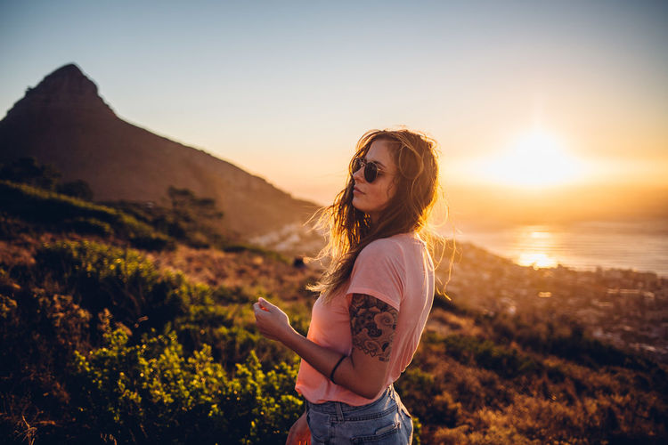 Young woman wearing sunglasses standing on land against sky during sunset