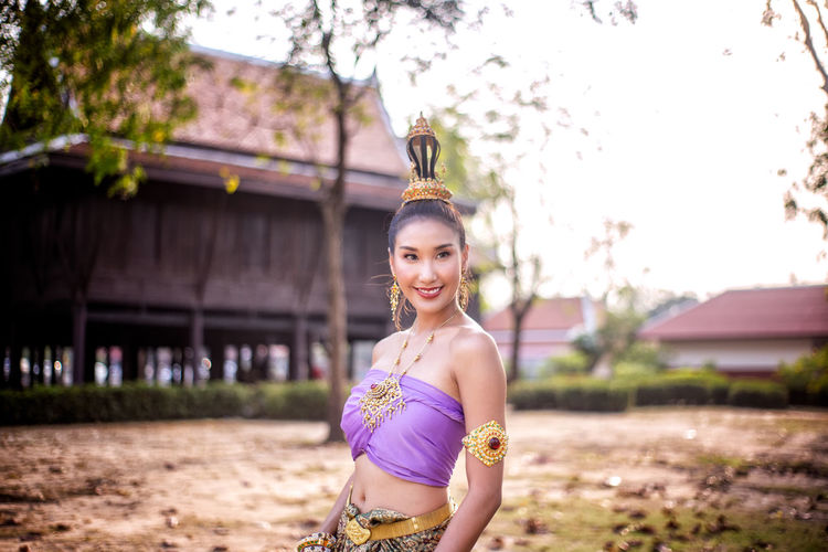 Smiling woman in traditional clothing looking away while standing against building
