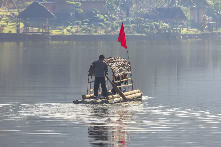 Rear view of man standing in wooden raft on lake