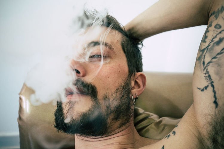 Close-Up Of Tattooed Man Smoking