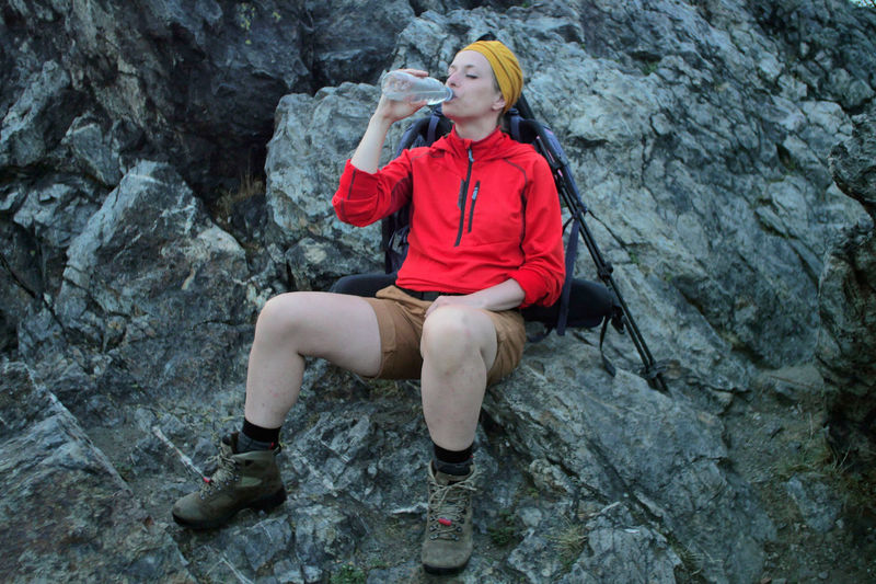 female hiker drinking water Alpine Backpacking Boots Camping Expedition Freedom Hiking Hydration Travel Trekking Woman Active Activity Adult Adventure Backpack Bottle Casual Clothing Caucasian Day Drinking Female Fitness Front View Full Length Hairstyle Leisure Activity Lifestyles Nature One Person Outdoors People Real People Red Rock Rock - Object Rock Formation Sitting Solid Trail Water Young Adult