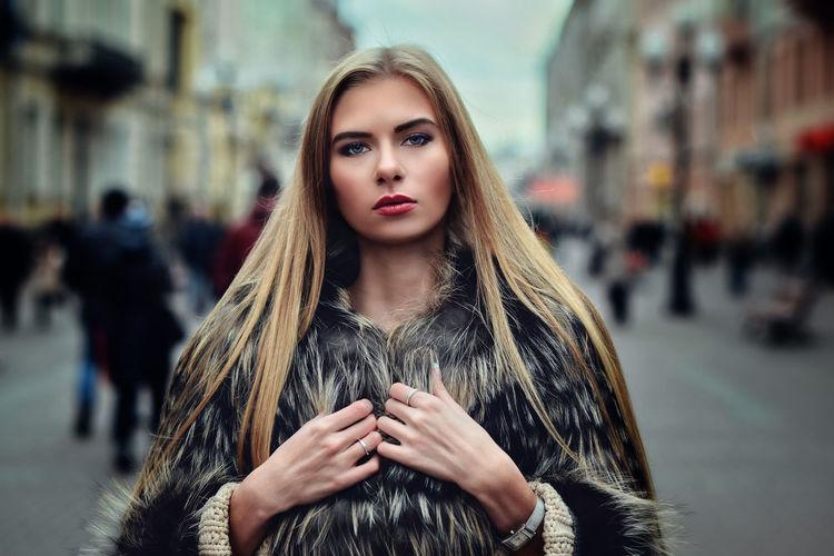 Portrait of beautiful young woman wearing fur coat on city street
