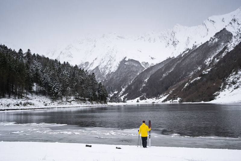 Rear view of person on snowcapped mountain by lake against sky