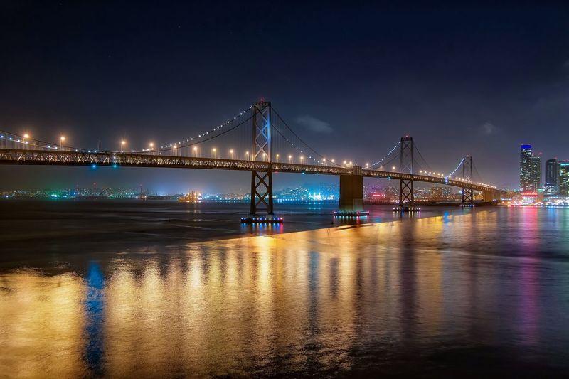 Low angle view of bay bridge over san francisco bay at night