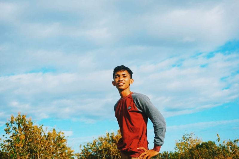 Smiling young man standing against sky