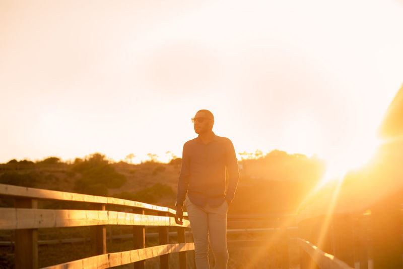 Rear view of man standing by railing against sky during sunset