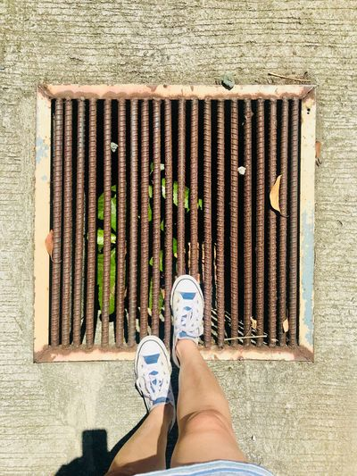 Directly above low section of woman standing on drain