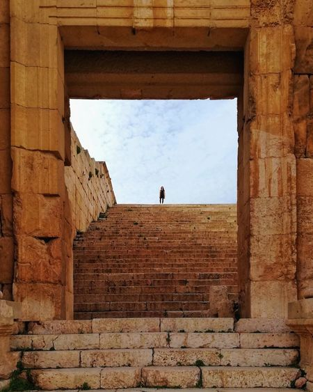 Distant view of woman standing on staircase against sky