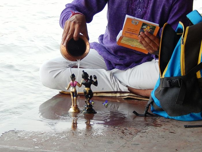 Low section of man pouring water on god figurine at beach