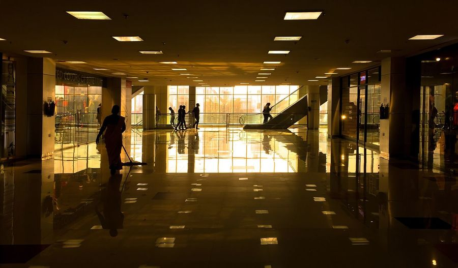 Interior of shopping mall with sweeper cleaning floor and people by escalator