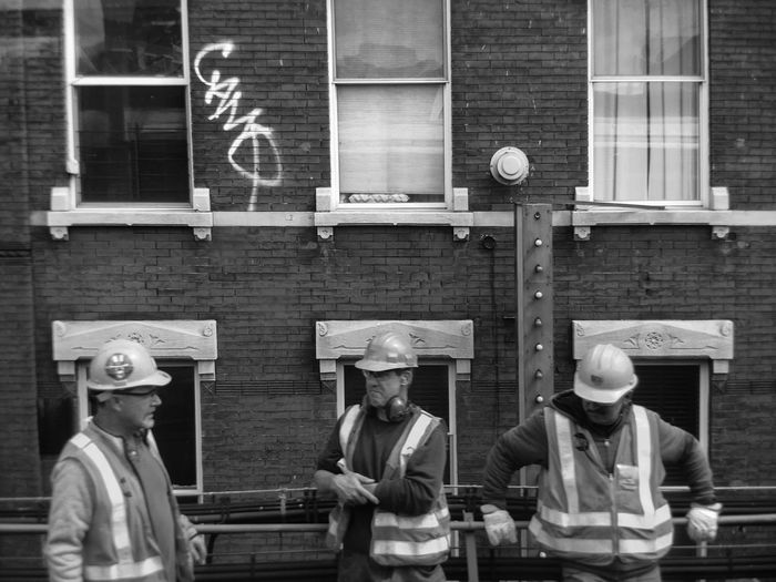 Construction workers against graffiti on building in city