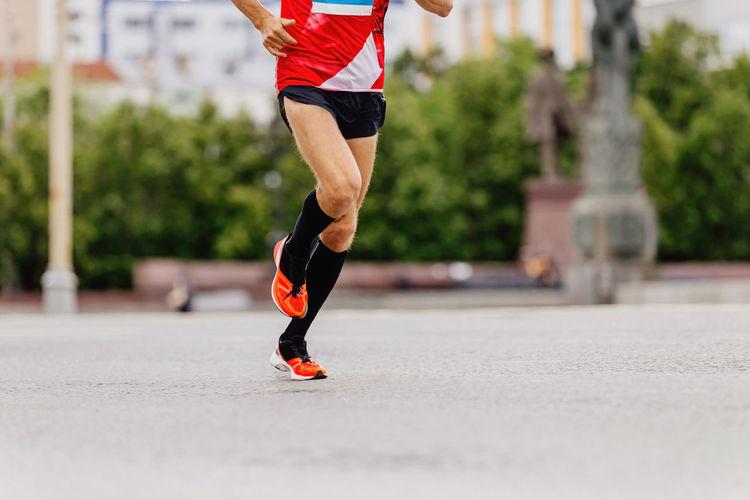 Man runner in black compression socks running city marathon