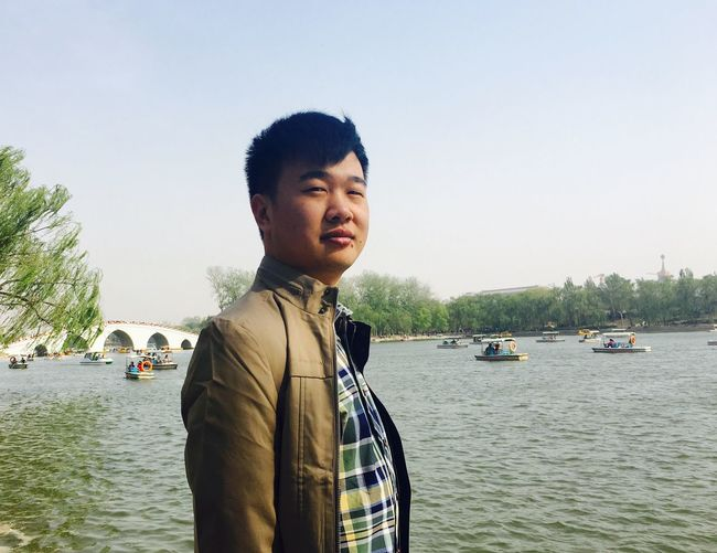 Portrait of young man by river against sky