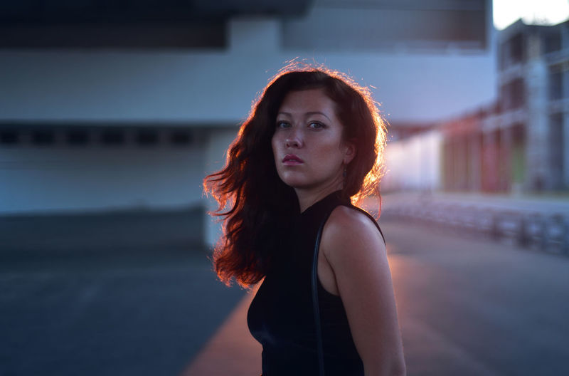 Architecture Beautiful Woman Beauty Beauty Skin Brown Hair Casual Clothing City Contemplation Focus On Foreground Hair Hairstyle Long Hair Looking Looking At Camera One Person Portrait Standing Sunset Young Adult