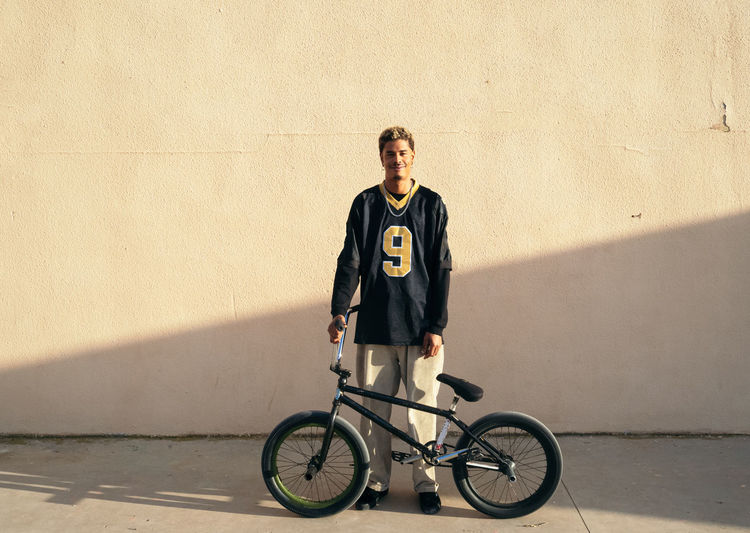 Portrait of young man with bicycle standing against wall