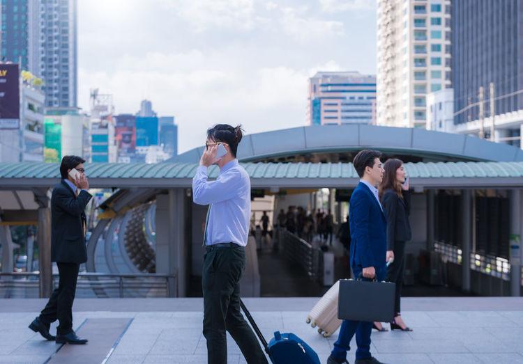 People Walking On Elevated Walkway Against Buildings In City