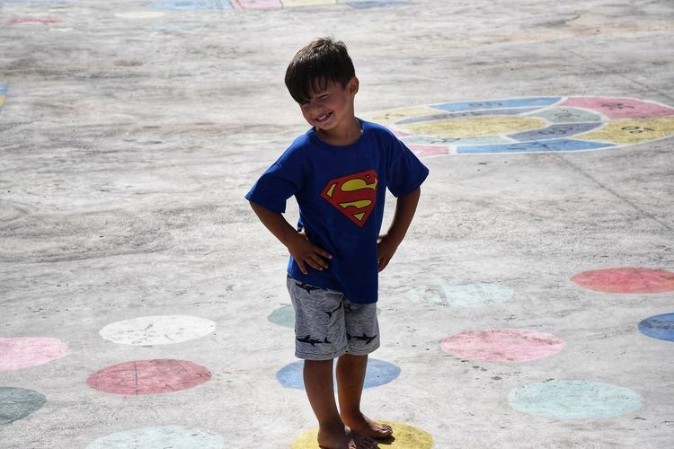 Full Length Of Boy Standing On Yellow Spot At Concrete Ground