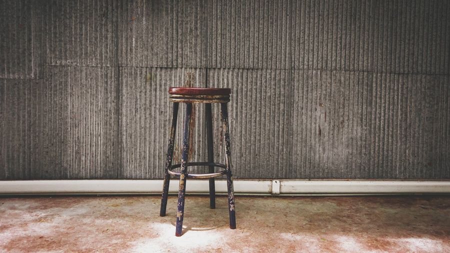 Vintage chair with galvanized wall and concrete floor background. copy space.