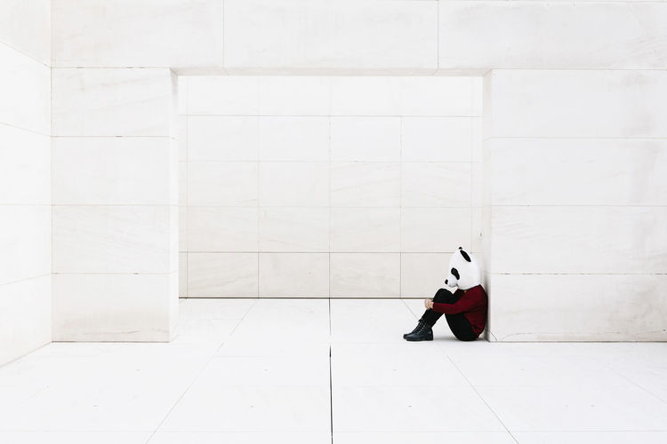 Man sitting on floor against white wall