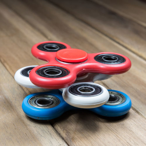 Fidget spinner stress relieving toy on wooden table Bearing Children Closeup Fidget Spinner Fidgetspinner Focus Game Hand Kid Latest Toy New Craze Plastic Play Spin Spinner Stress Toy