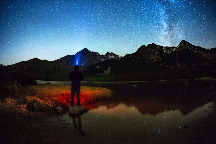 Silhouette man standing by lake against sky at night