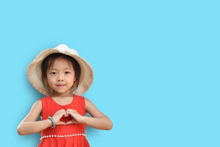 Full length of cute girl standing against blue background