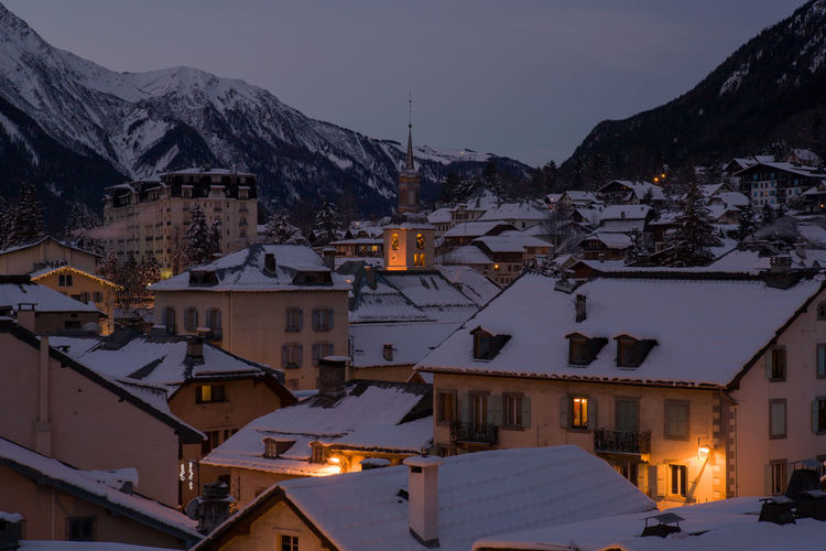 Snow covered houses in town at dusk
