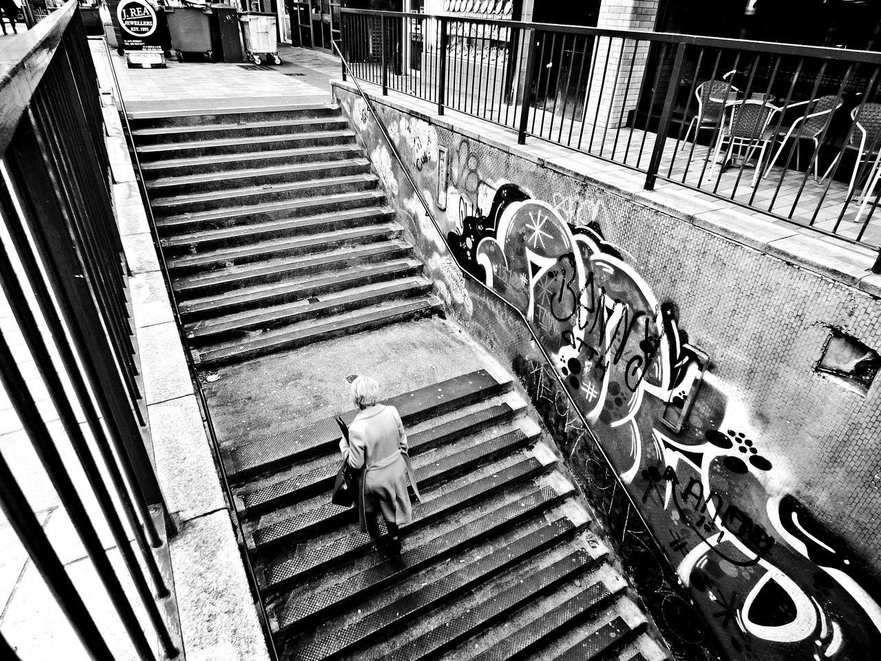 high angle view, railing, steps, steps and staircases, staircase, metal, built structure, day, real people, men, architecture, outdoors, working, people