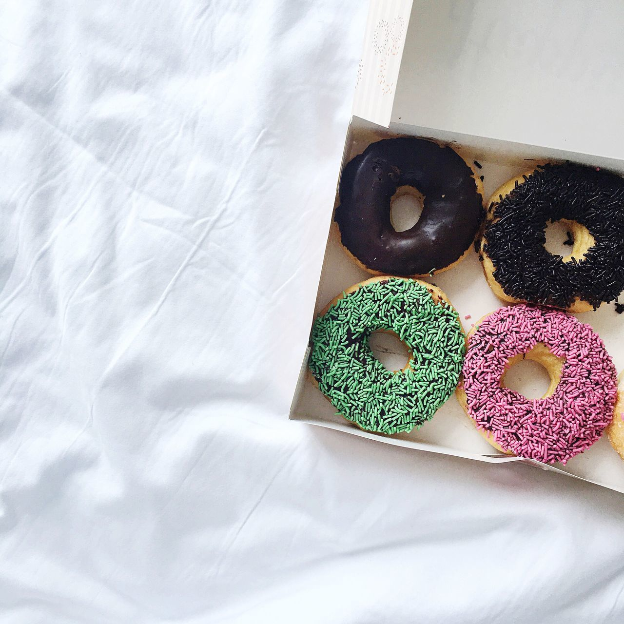 High angle view of donuts in box on tablecloth