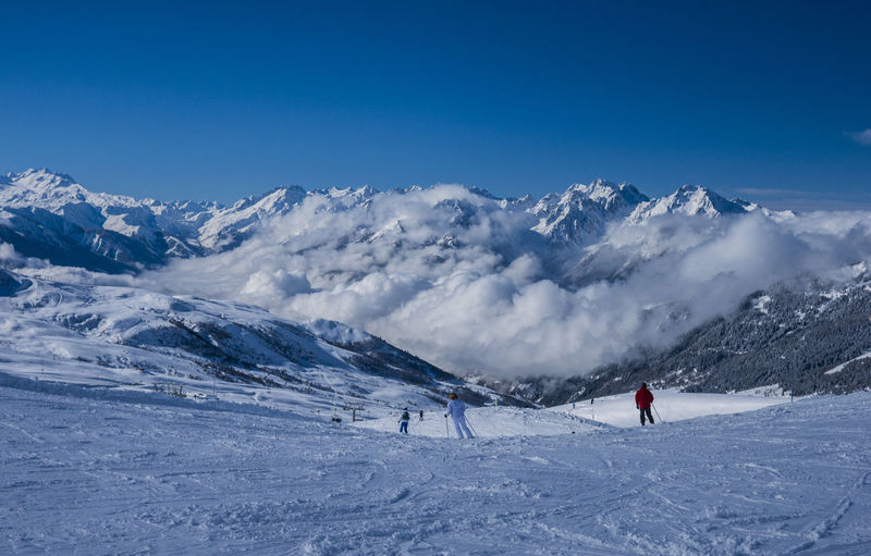 People skiing on snowcapped mountain against clear blue sky