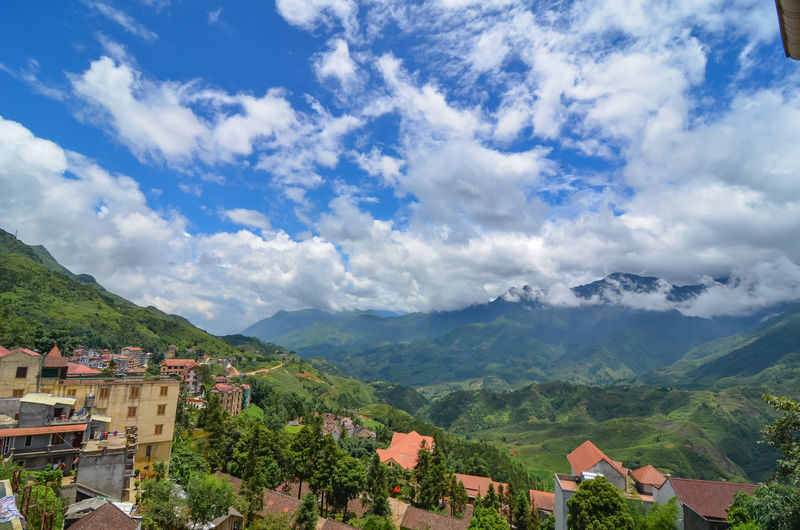 Scenic View Of Townscape And Mountains Against Sky