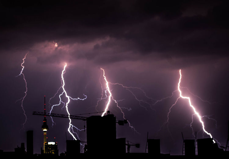Lightning In Sky Over Silhouette Buildings At Night