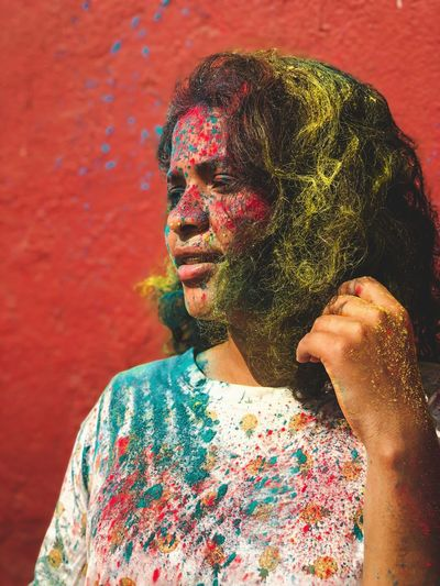 Woman with multi colored powder paint on face against wall during festival