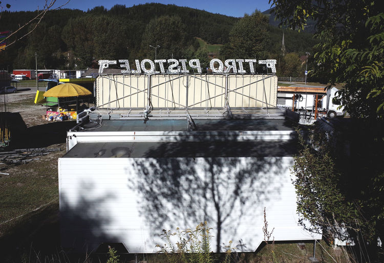 Amusementpark Backyard City Life Dramatic Angles Luna Park Mountain Outdoors Pistol Shadow Shooting Sign Street Structure Trailer Trailer Park Trucks View From Behind Writing