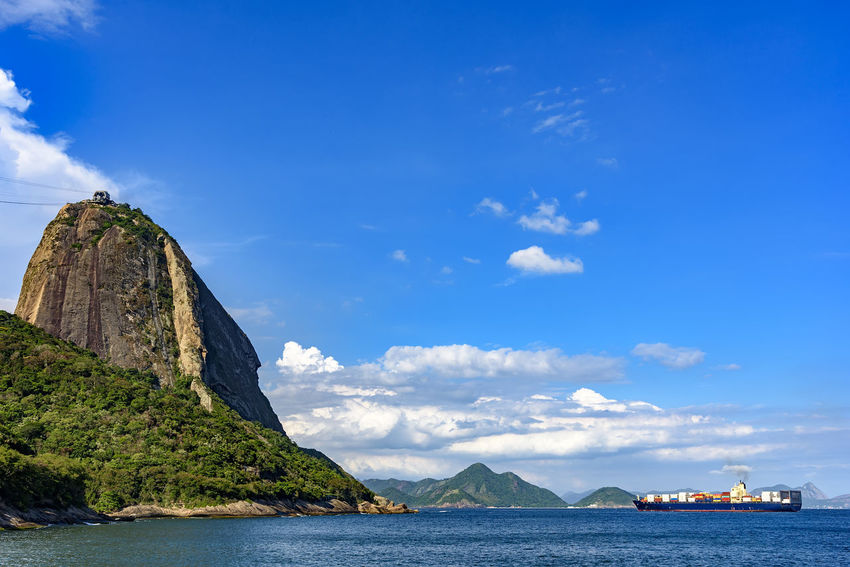 Freighter ship passing the side of the Sugar Loaf hill when entering the Bay of Guianabara Brazil Cargo Ship Logistics Rio De Janeiro Transportation Blue Cliff Day Guanabara Bay Hill Mountain Nature Nautical Vessel No People Outdoors Rock - Object Scenics Sea Seascape Sky Sugarcane Tranquil Scene Tranquility Travel Destinations Water